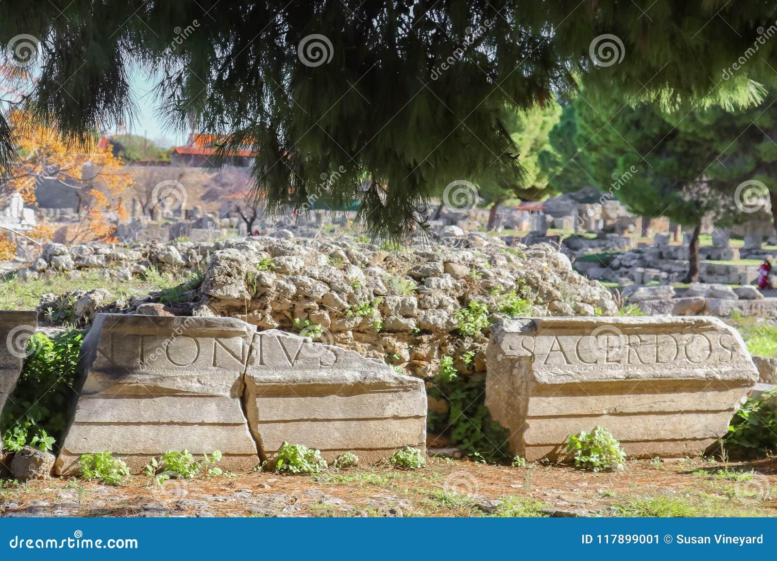 De resten van steen met het Roman schrijven sneden op hen voor puin en onder pijnboombomen in Corinth Griekenland