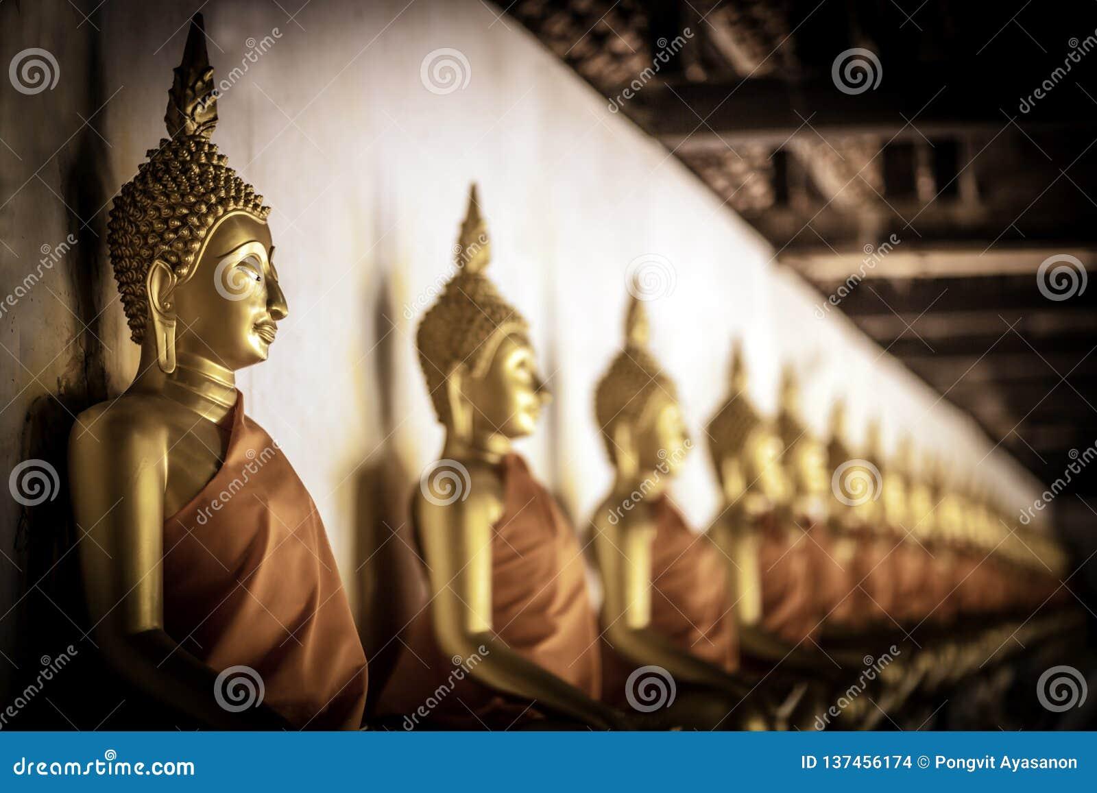 De rij van de gouden zitting van meditatieboedha komt voor de standbeelden binnen gang in Wat Phutthaisawan, Si Ayutthay van Phra
