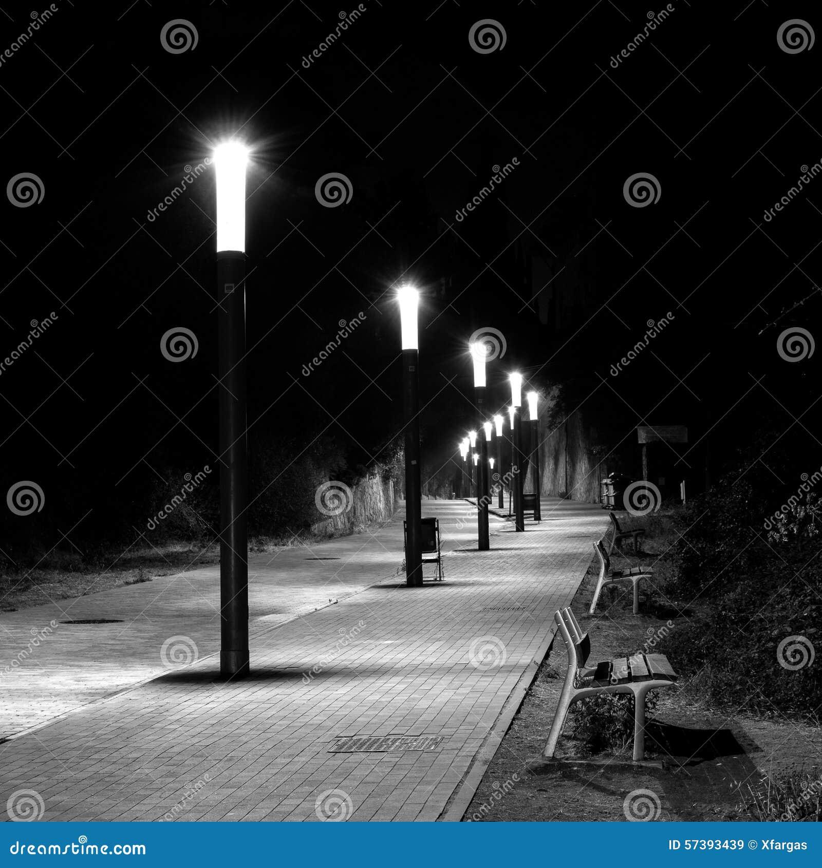 De rij van straatlantaarns in gebogen en cobbled Straat