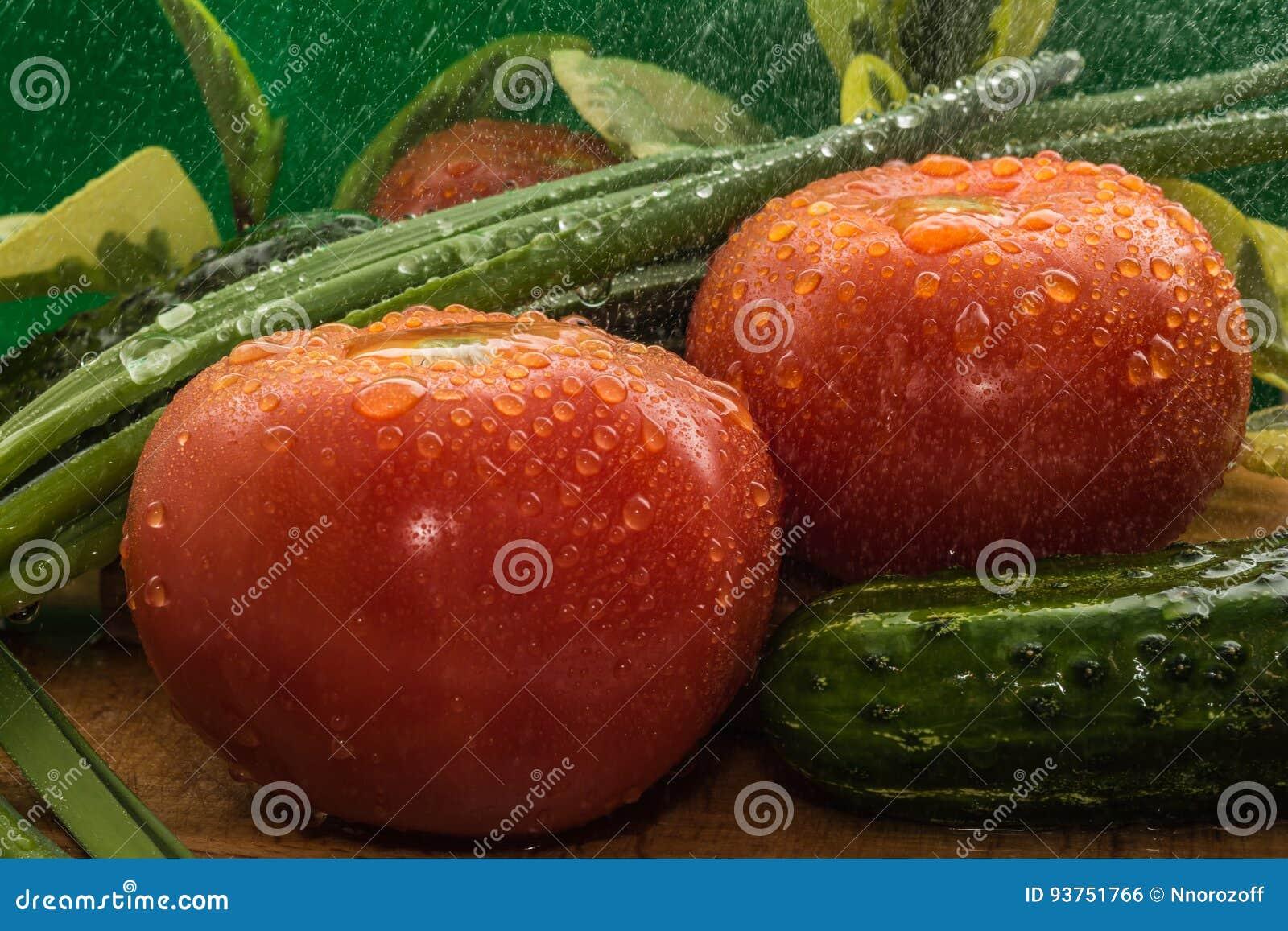 De rijpe rode tomaten, groene komkommers, groene uiveren zijn behandeld met grote dalingen van water