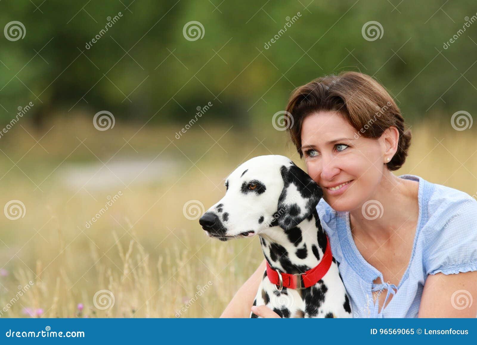 De rijpe vrouw knuffelt een Dalmatische hond in een weide openlucht