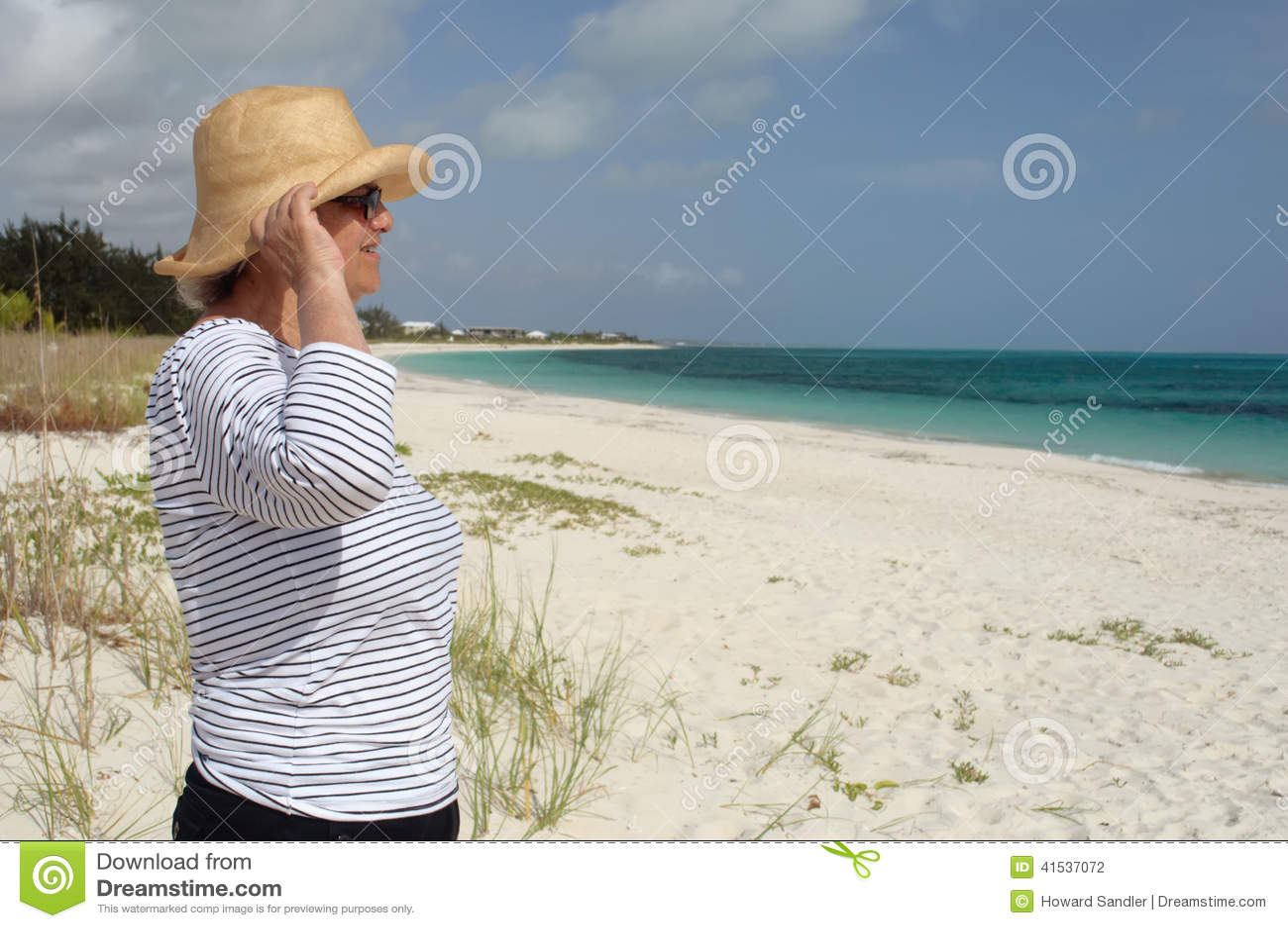 De rijpe vrouw in profle kijkt uit op zee