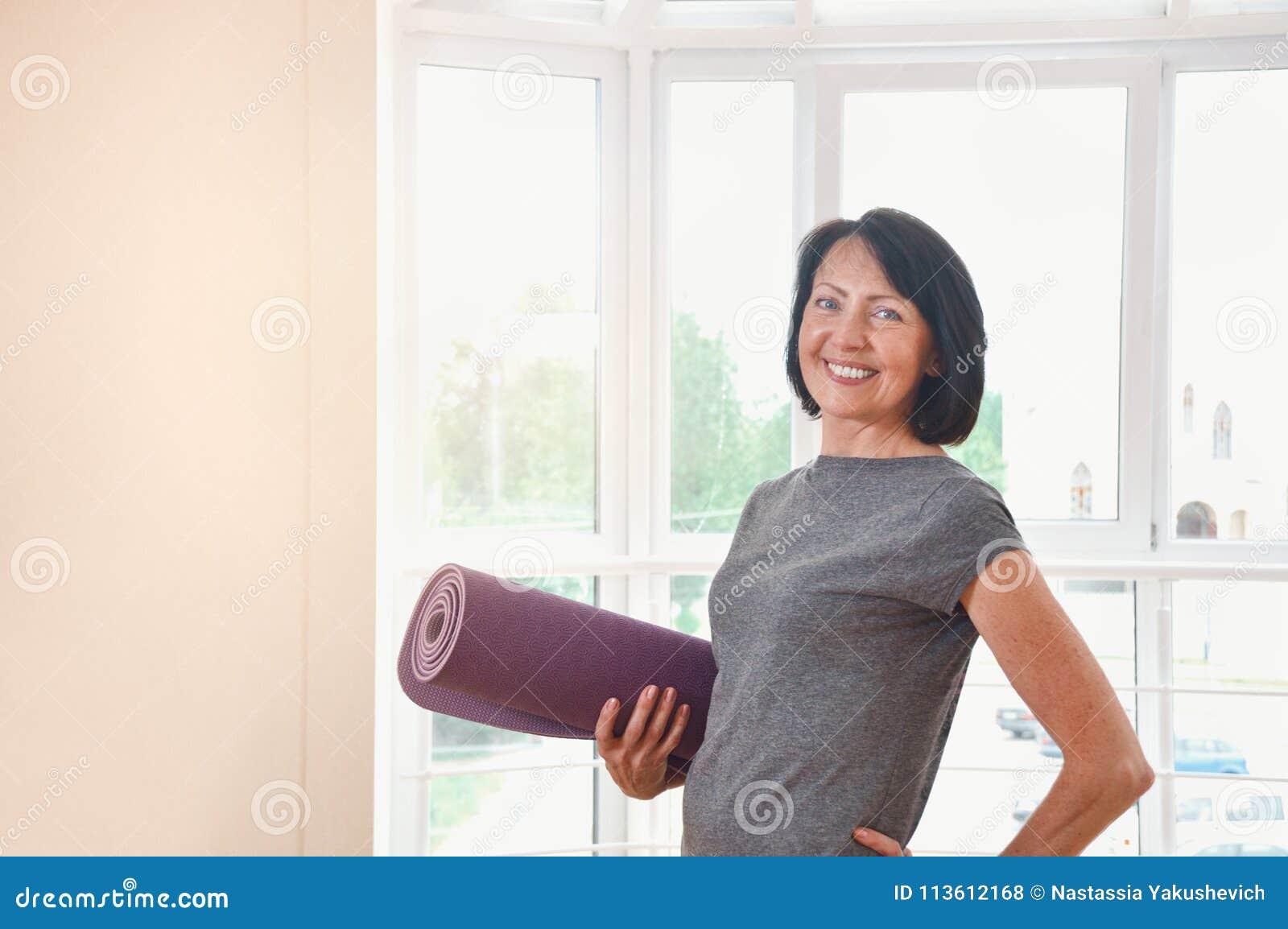 De rijpe vrouwenholding rolde oefeningsmat bij gymnastiek op