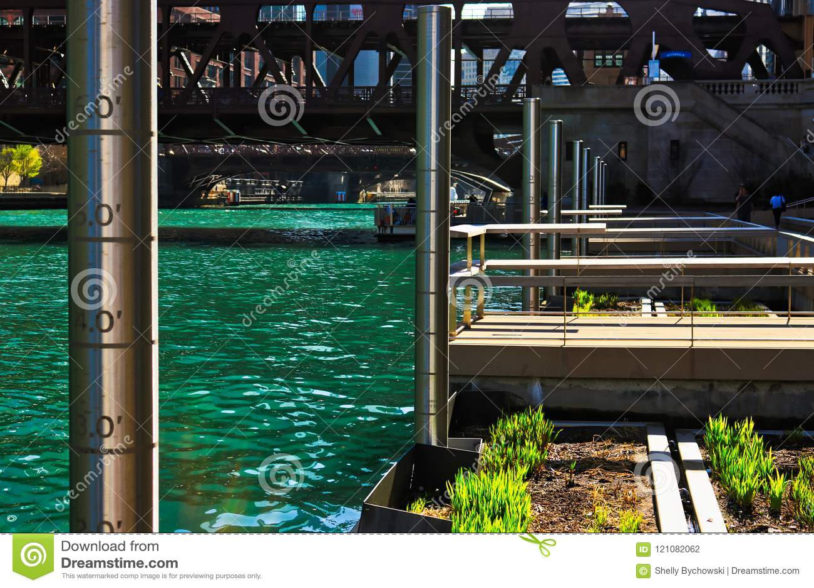 De Rivier van Chicago met metingspolen, de drijvende bedden van de ecosysteemtuin, en visserijpijlers langs riverwalk