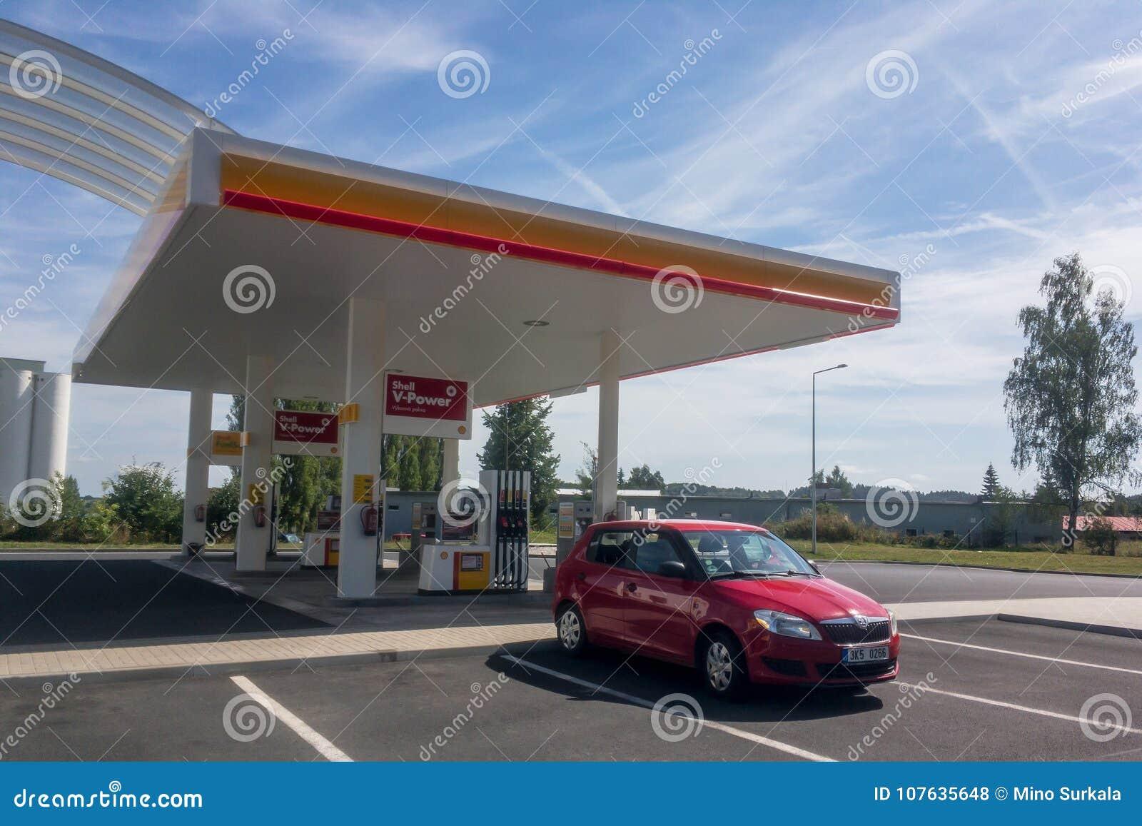 De rode auto van Skoda Fabia bij Shell-benzinestation