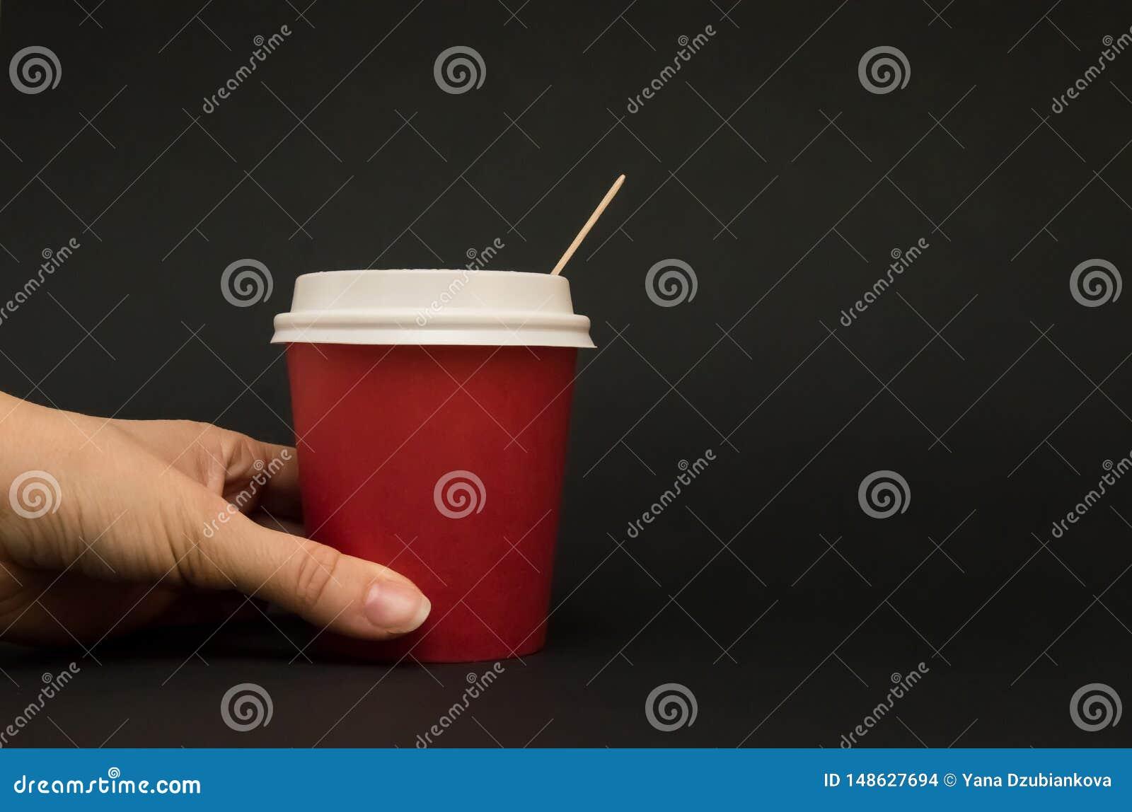 De rode document kop voor koffie met een deksel op een zwarte achtergrond, hand houdt een document kop