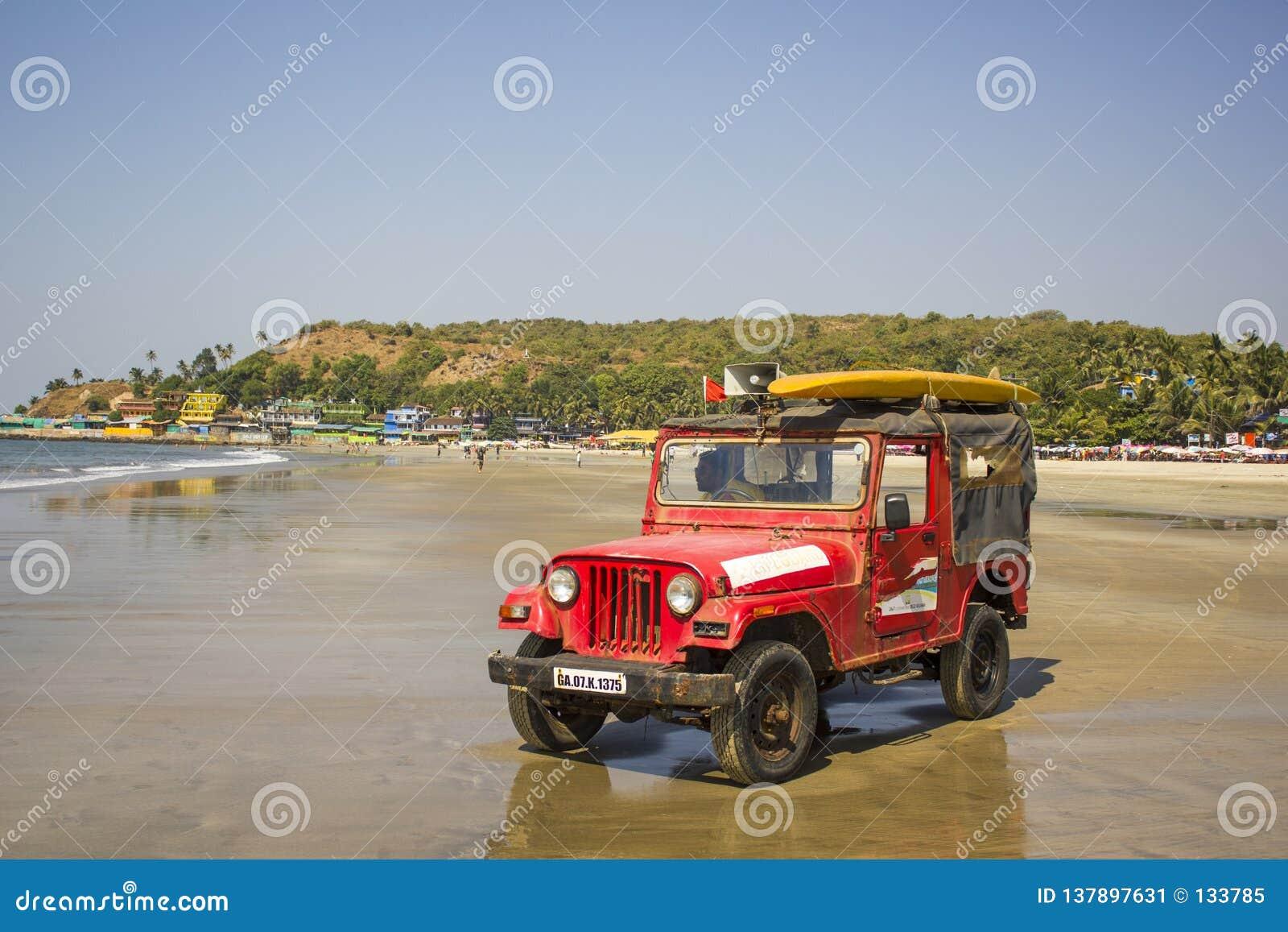 De rode reddingsauto met een luidspreker en een gele branding schepen op het dak, op een zandig strand in