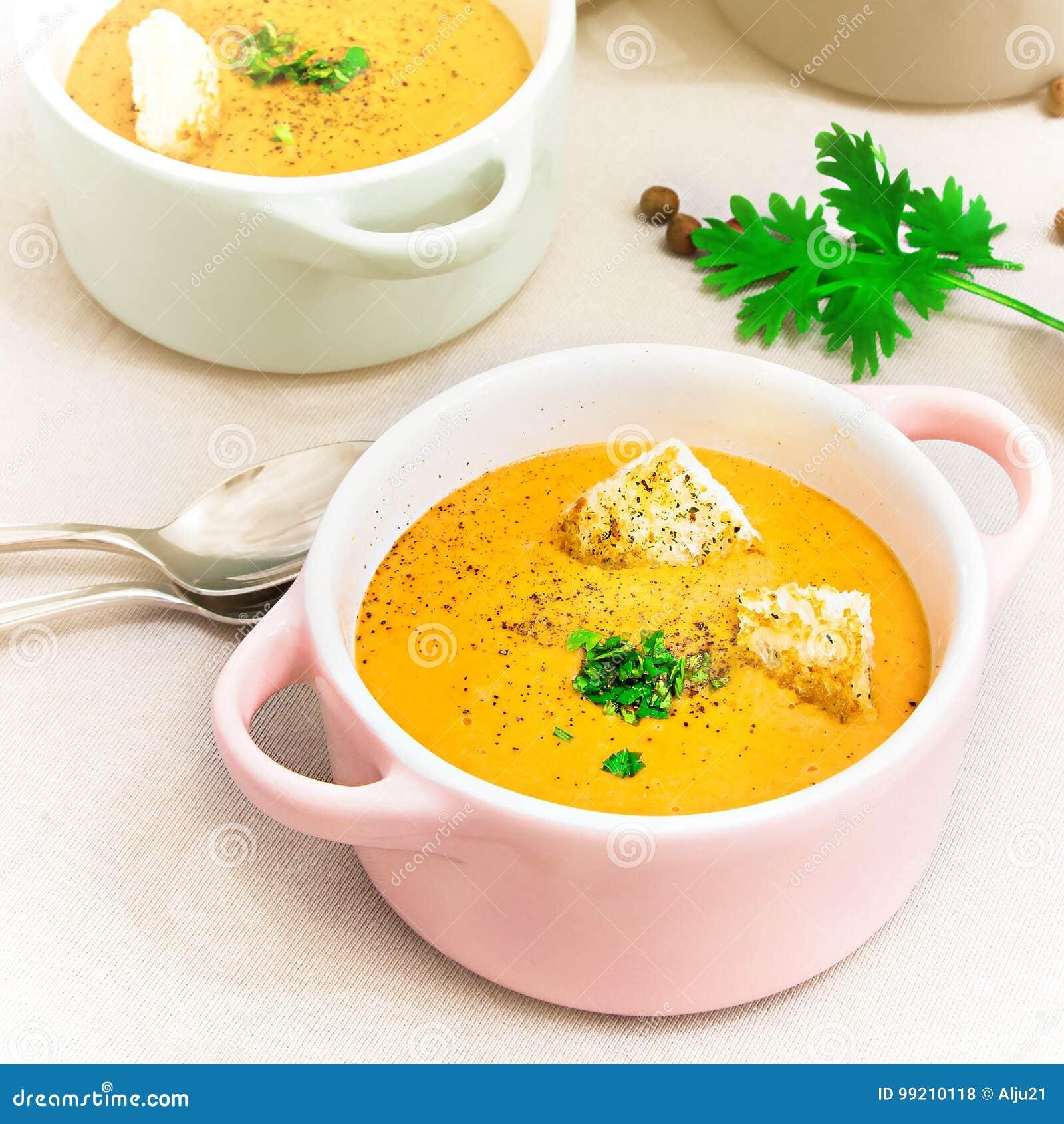 De rode soep van de linzenroom met beschuiten in kleine dienende potten of kom