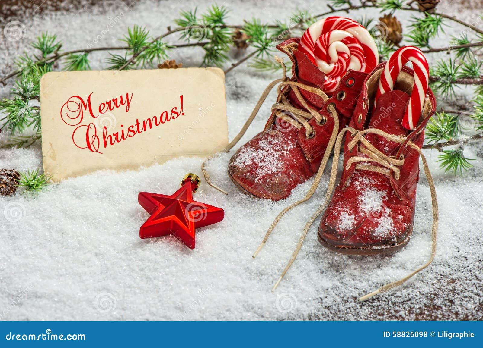 De rode sterren van de Kerstmisdecoratie, snoepjes en antieke babyschoenen