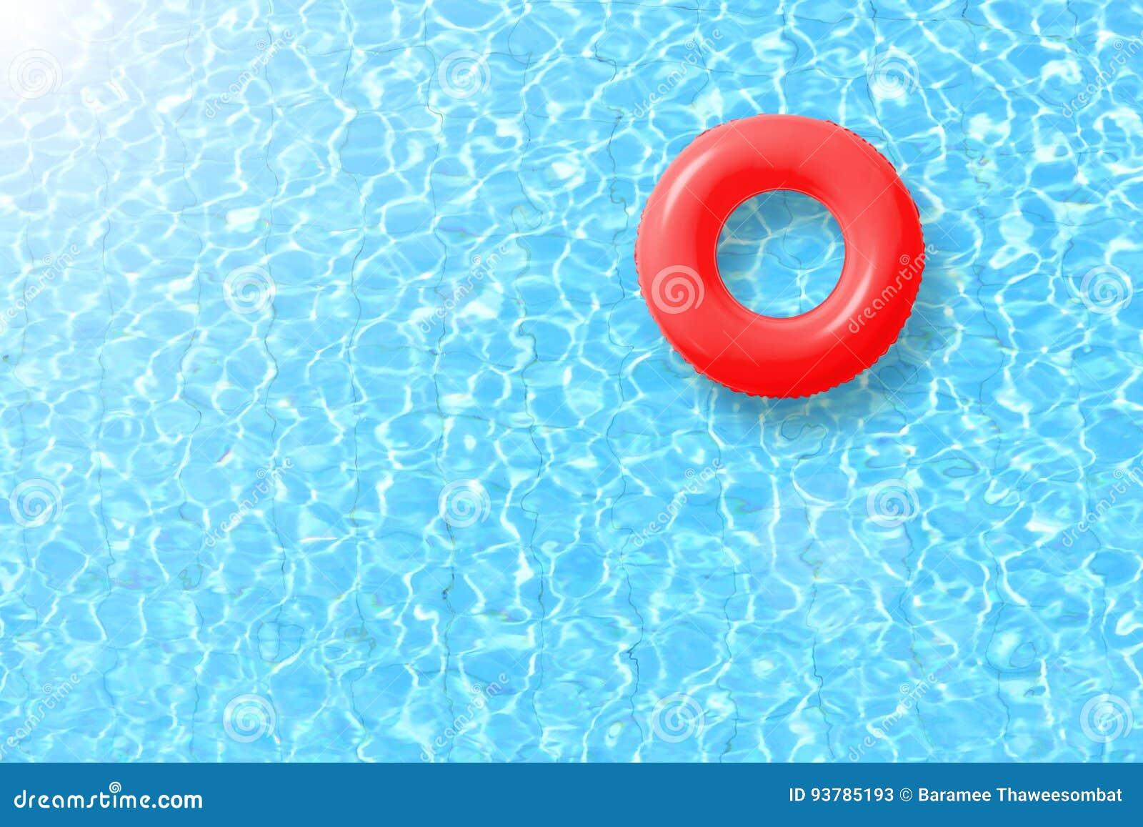 De rode vlotter van de zwembadring in blauw water en heldere zon