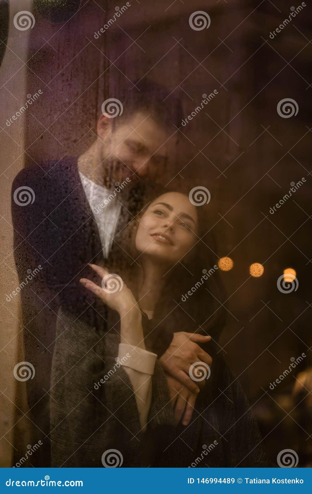 De romantische het houden van kerel koestert zijn gelukkig meisje die zich achter een nat venster met lichten bevinden