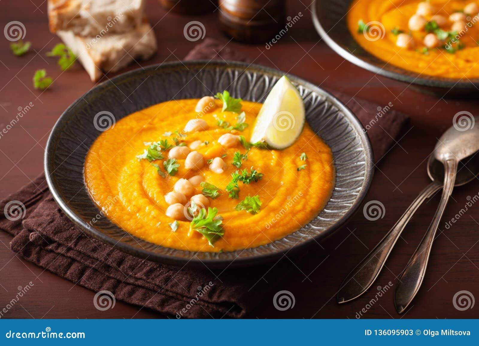 De romige soep van de wortelkikkererwt op donkere rustieke achtergrond