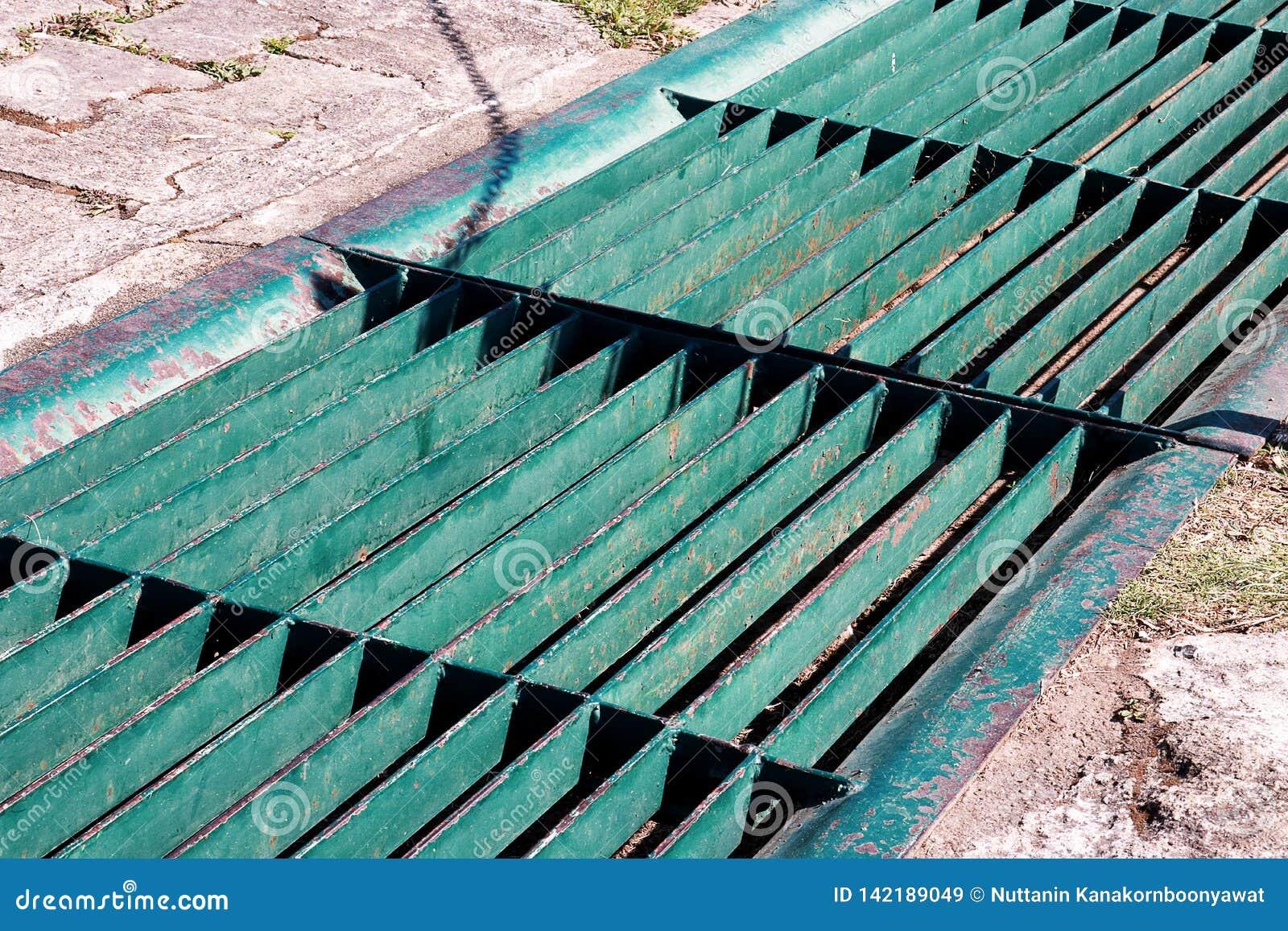 De rooster van het gotenafvoerkanaal, afvoerkanaaldekking Wegafvoerkanalen - riooldekking Ijzerrooster van waterafvoerkanaal op d