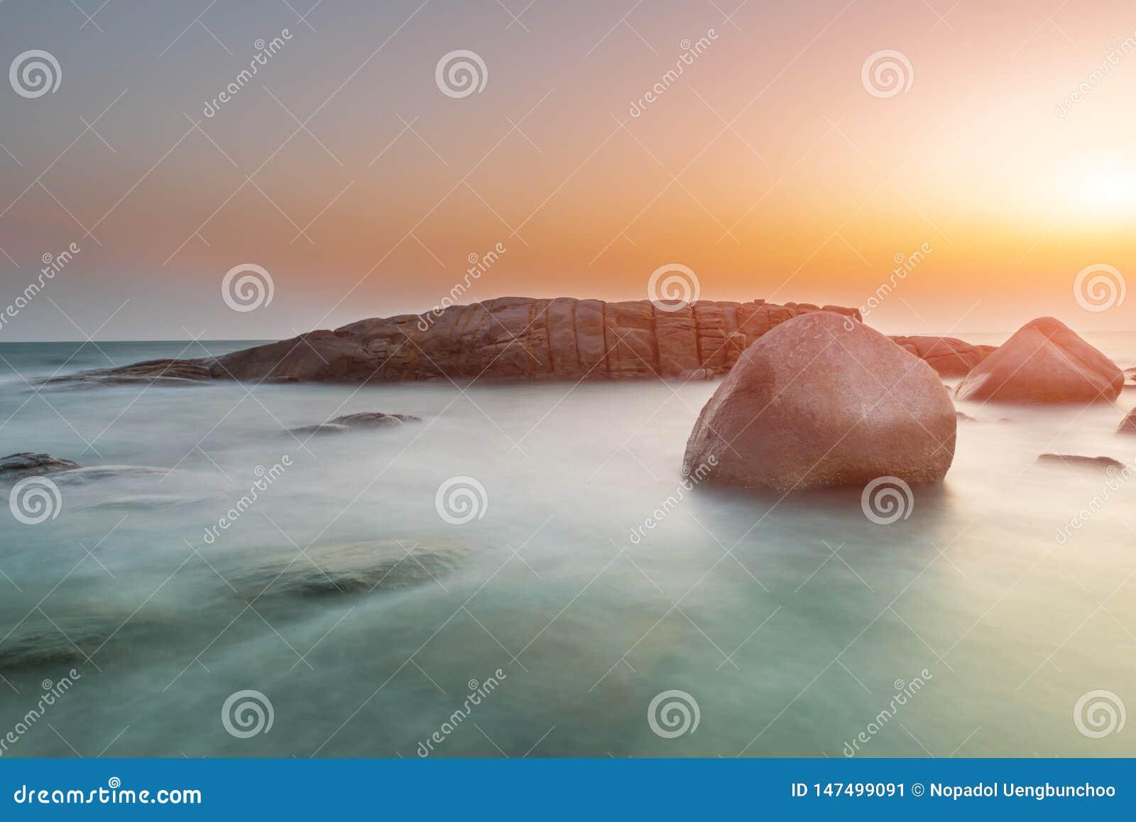 De rots en het overzees in de kleur van zonsondergangtijd