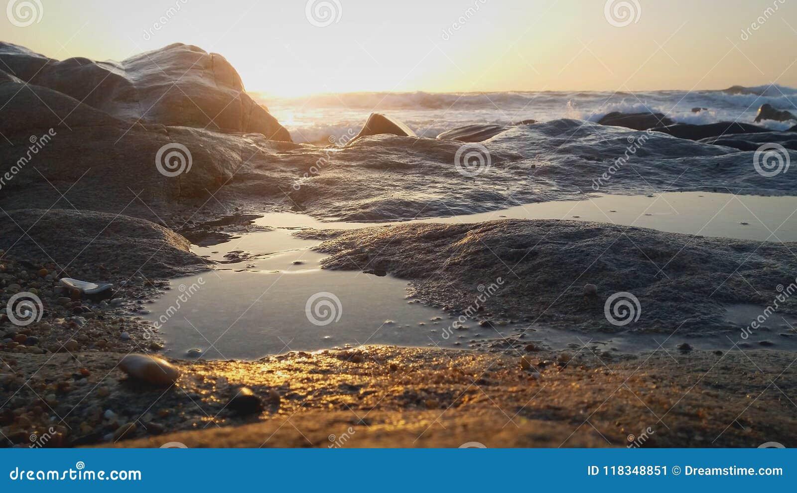 De rotsen van de zonsondergang op strand