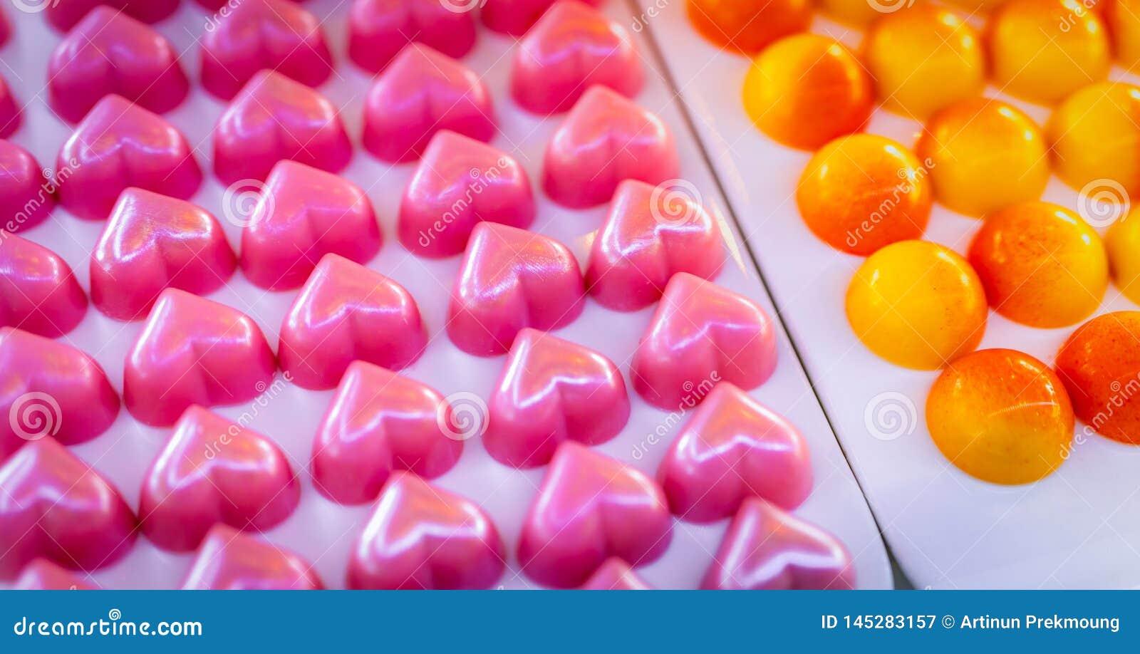De roze chocolade van de hartvorm De daggift van Valentine ` s Witte chocolade ganache met roze geur op witte plaat Ondiepe diept