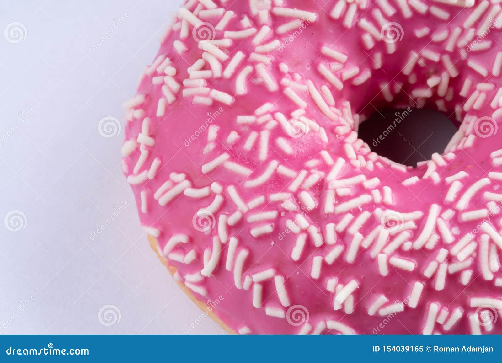 De roze doughnut op witte achtergrond, sluit omhoog macro