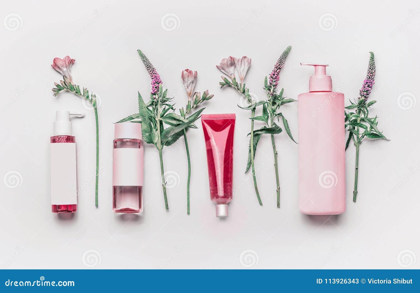 De roze kruiden natuurlijke gezichtscosmetischee producten plaatsen met kruiden en bloemen op witte achtergrond