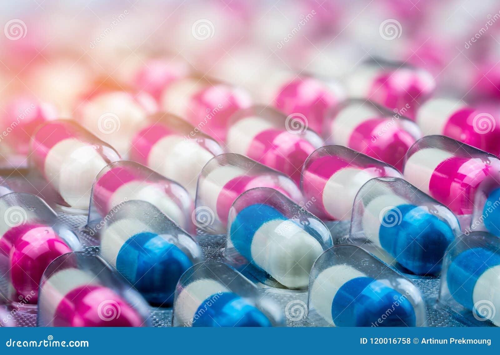 De roze-witte en blauw-witte pillen van de antibioticacapsule in blaarpak Antimicrobial drugweerstand Farmaceutische Industrie