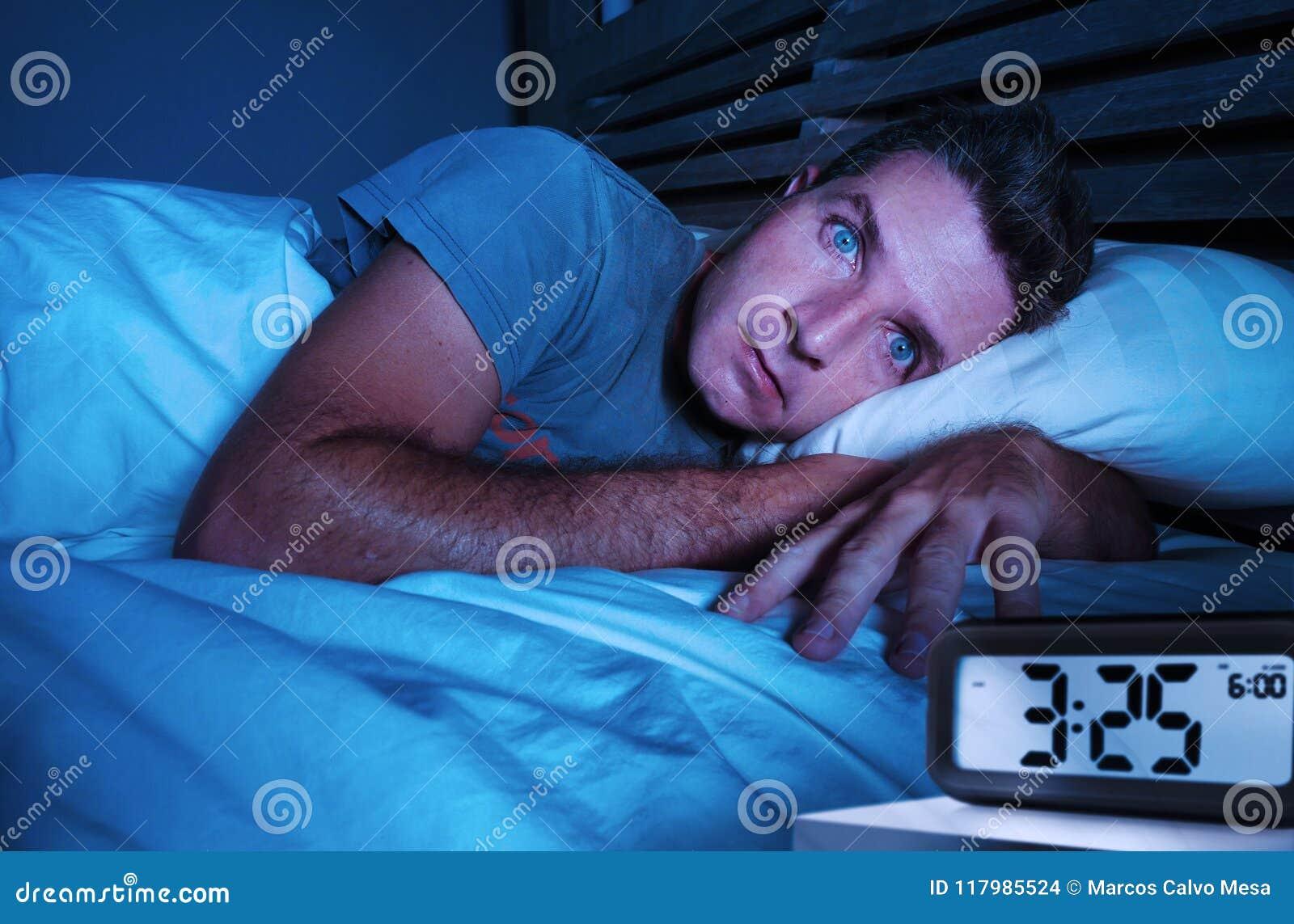 De rusteloze ongerust gemaakte jonge aantrekkelijke mens wakker bij nacht die liggen op is