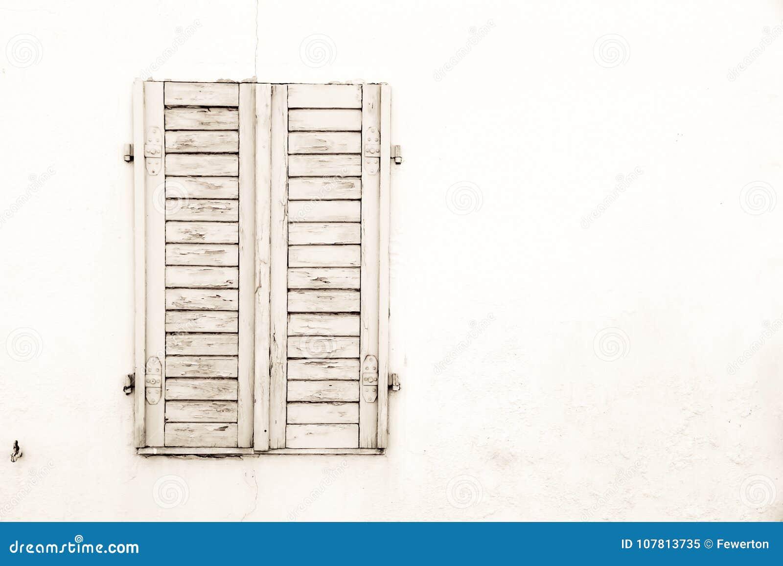De rustieke oude grungy en doorstane witte grijze houten gesloten vensterblinden met schil schilderen
