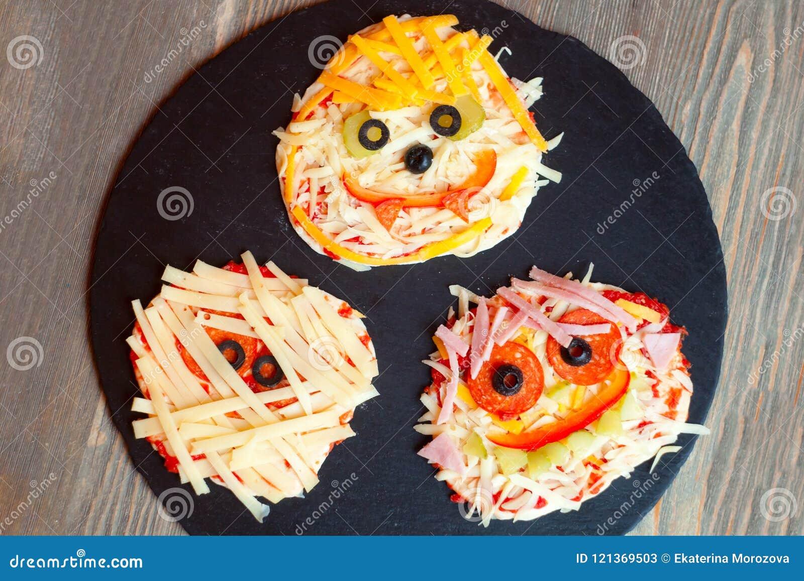 De ruwe Halloween-pizza met monsters, boven scène met decor op een zwarte plaat treft voor gebakken voorbereidingen, idee voor he