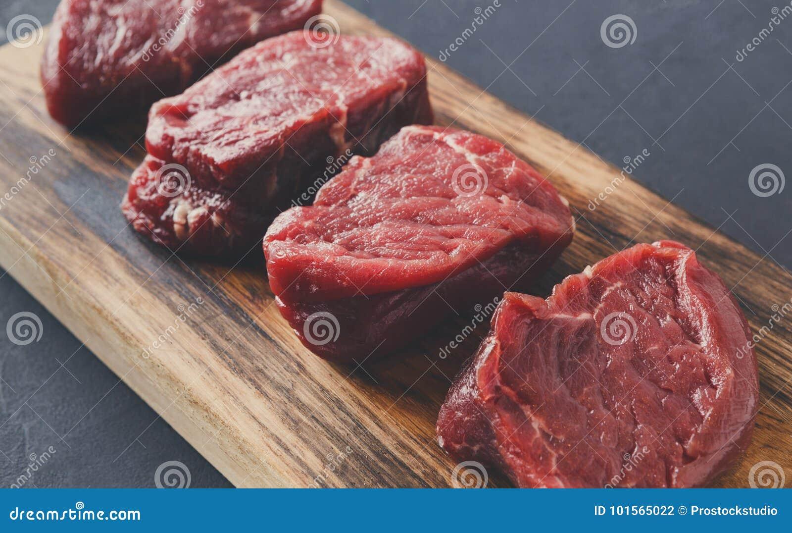 De ruwe lapjes vlees van het rundvleesfilethaakwerk mignon op houten raad bij grijze achtergrond