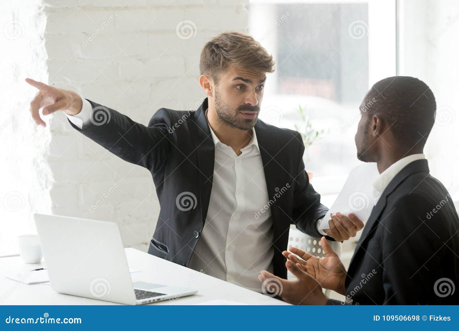 De ruwe witte partner het vertellen zwarte zakenman gaat zijn bureau weg