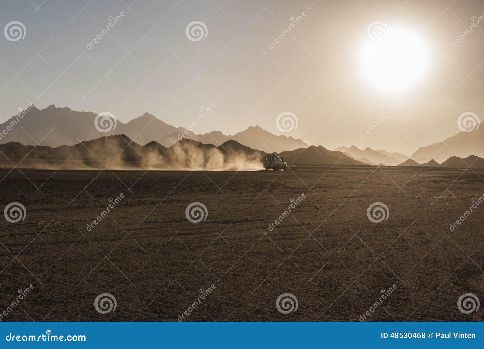 De safari del camino en desierto con puesta del sol
