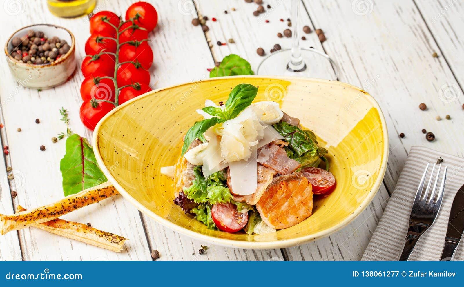 De Salade van Caesar met Zalm mengeling van salades, kersentomaten, parmezaanse kaaskaas, basilicum Een schotel in een ceramische