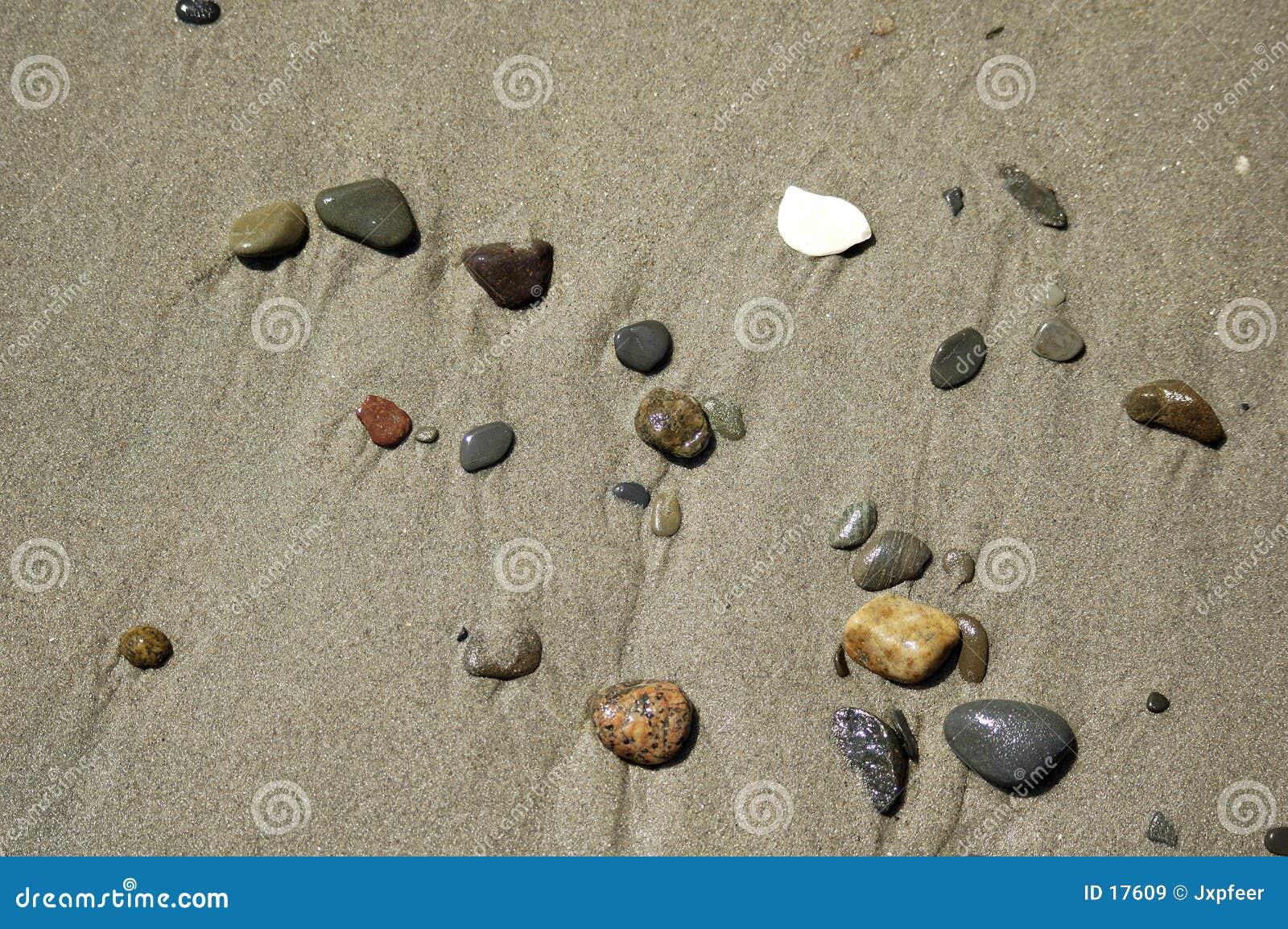 De scène van het strand - kiezelstenen in het zand