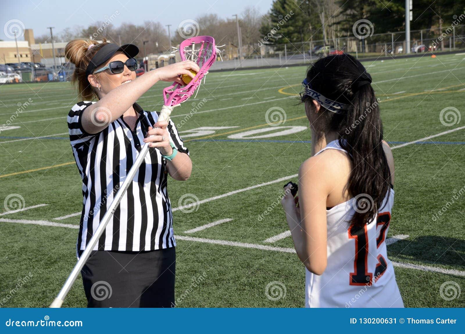 De scheidsrechter controleert een lacroosestok bij een spel van de meisjeslacrosse