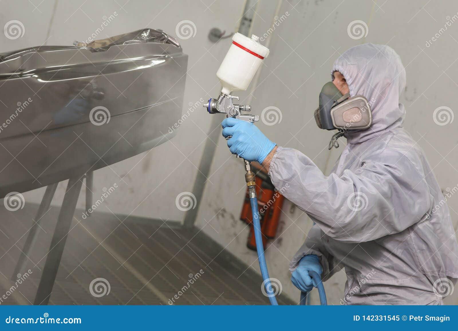 De schilder schildert het autodetail in de het schilderen kamer