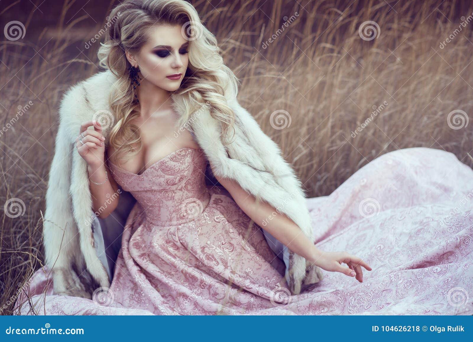 Download De Schitterende Blonde Dame Met Luxuriant Kapsel Die As Dragen Nam De Zitting Van De Baltoga In Droog Gras Toe Stock Foto - Afbeelding bestaande uit sloten, meisje: 104626218