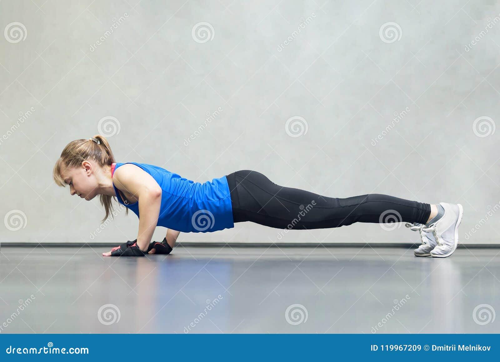 De schitterende blondevrouw die en wat opwarmen doen duwt UPS de gymnastiek, de gezonde levensstijl van het Sportenconcept en de