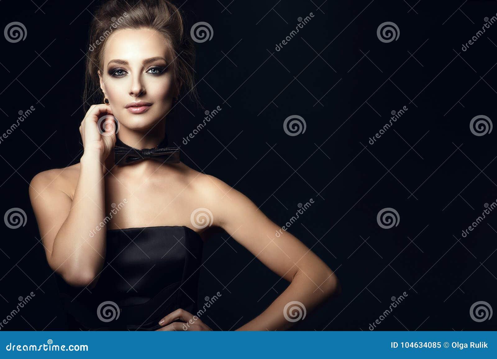 De schitterende glamvrouw met mooi maakt omhoog en updohaar die zwarte korsetkleding en vlinderdas op haar hals dragen
