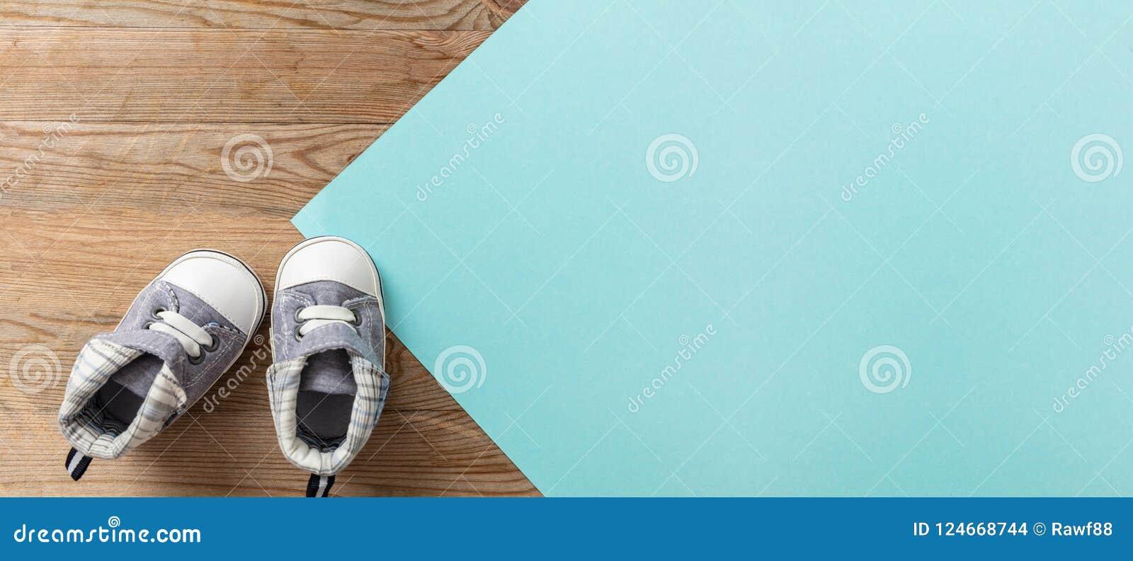 De schoenen van de babyjongen op pastelkleur blauwe en houten achtergrond, banner