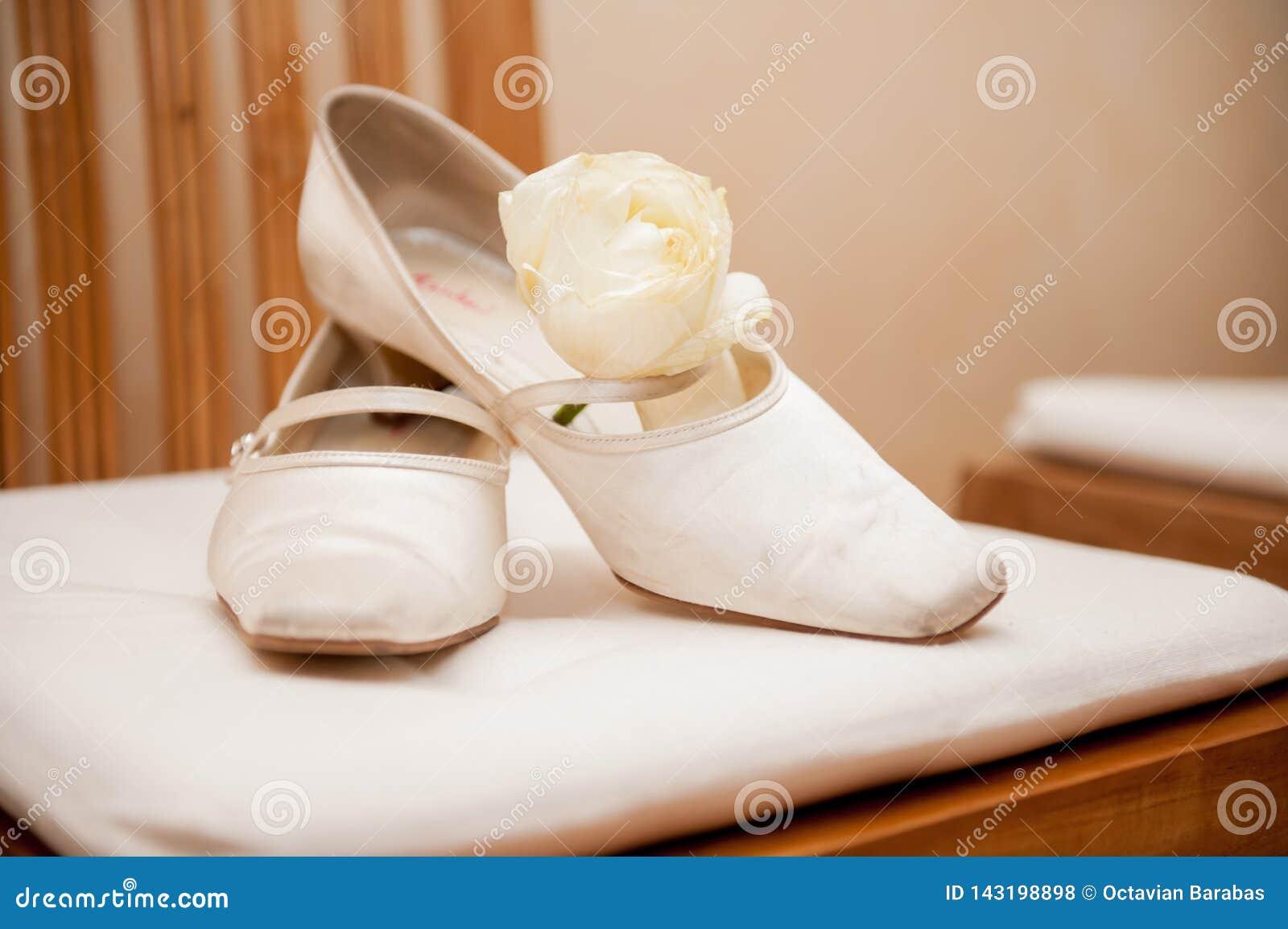 De schoenen van het bruidhuwelijk op stoel met namen toe