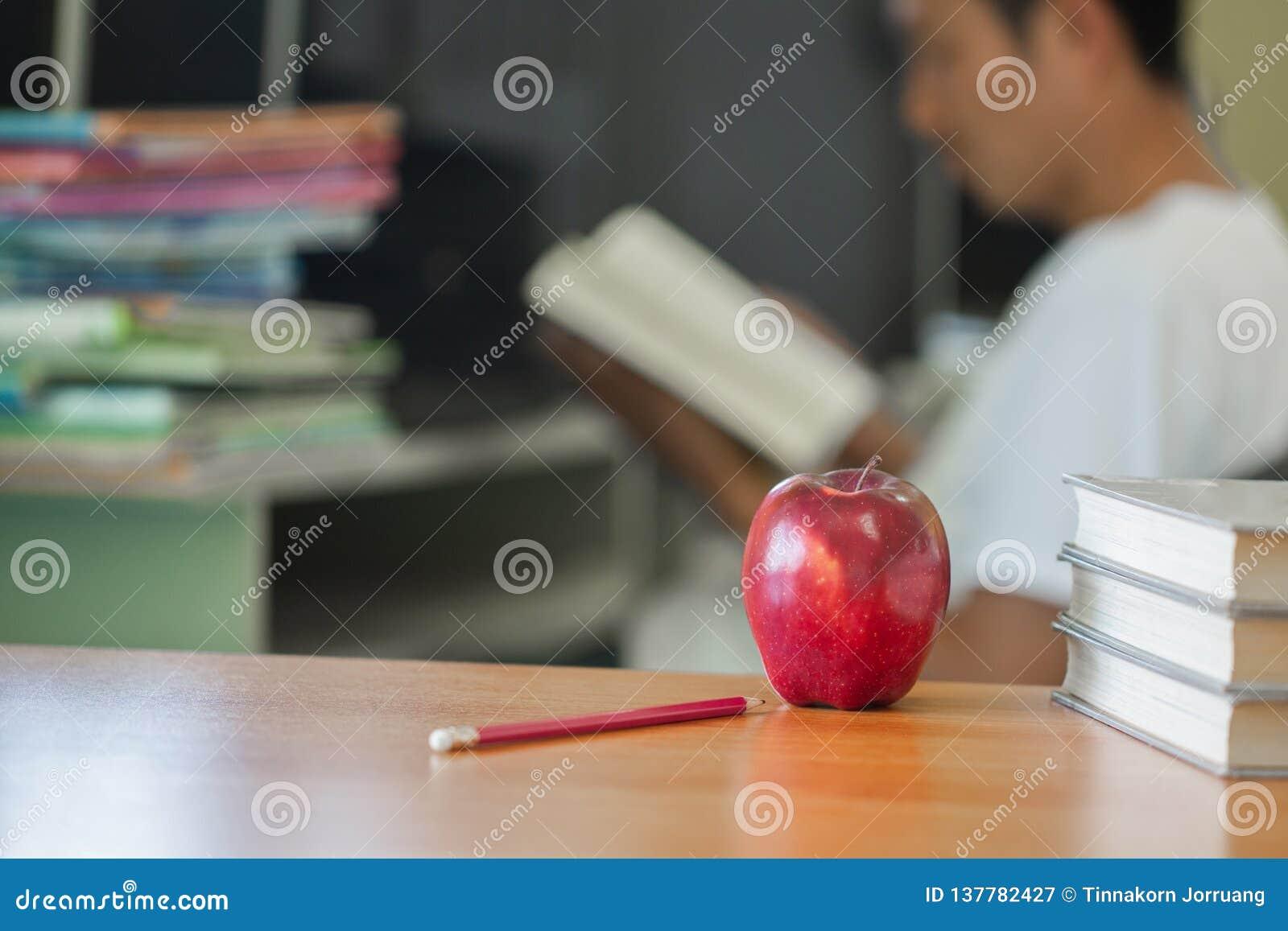 De school als thema had beeld bestaand uit een appel en uit een stapel van boeken de achtergrond een mensenzitting lezend een boe
