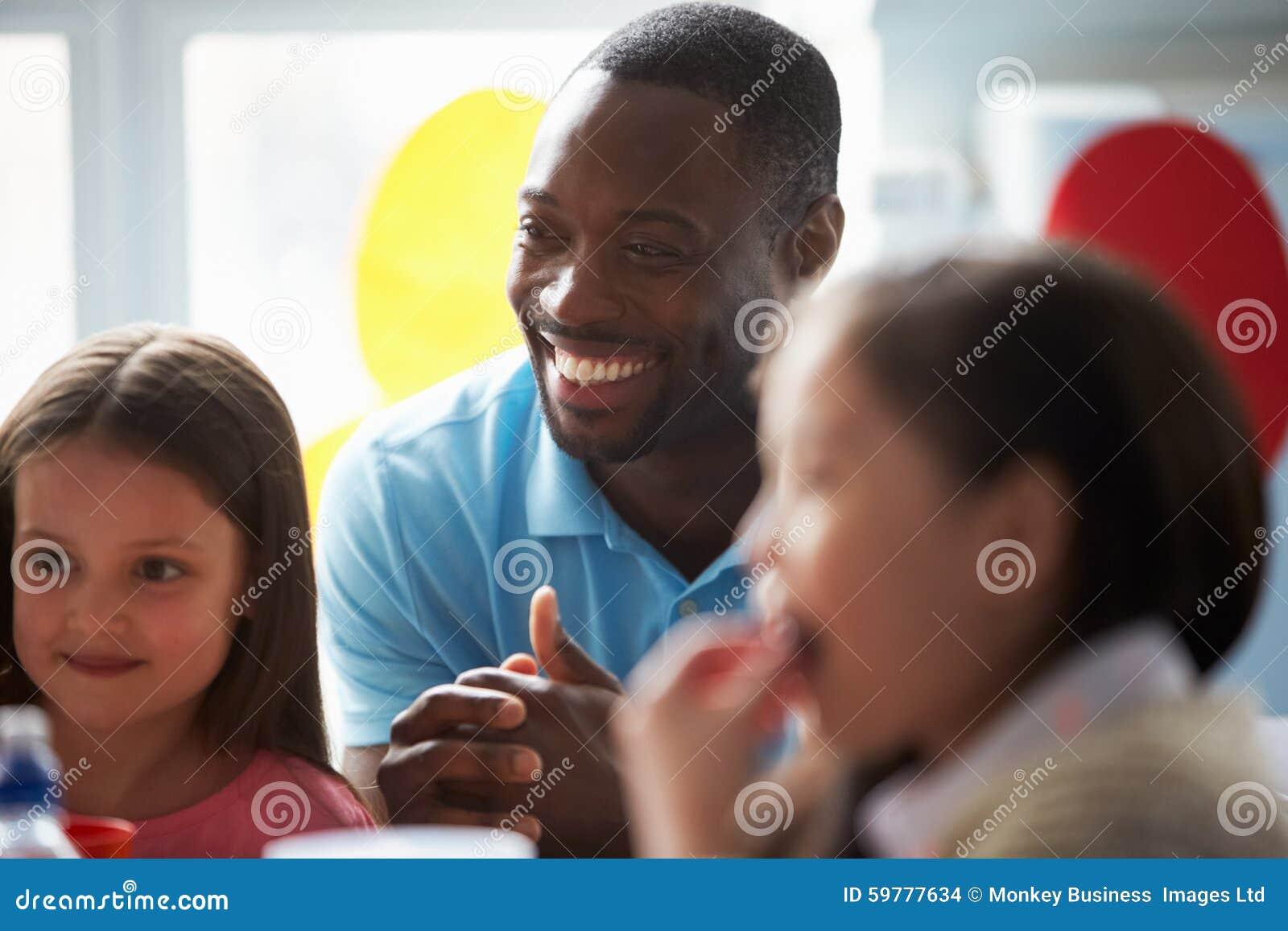 De Schoolmaaltijd van leraarssupervising children eating