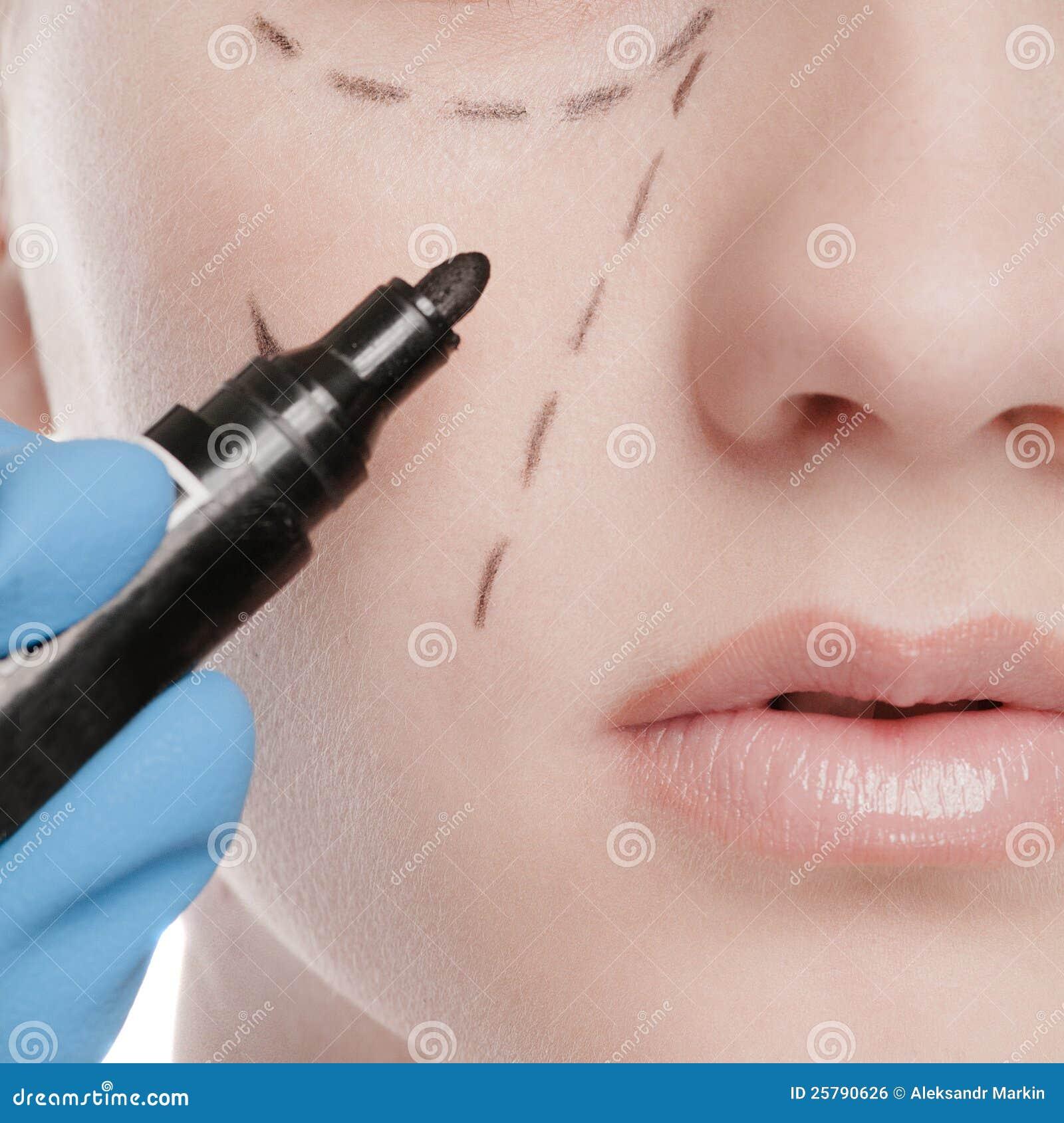 De schoonheidsspecialist trekt correctielijnen op vrouwengezicht