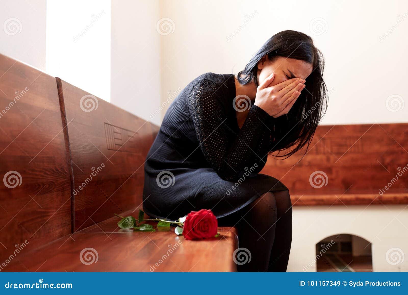 De schreeuwende vrouw met rood nam bij begrafenis in kerk toe