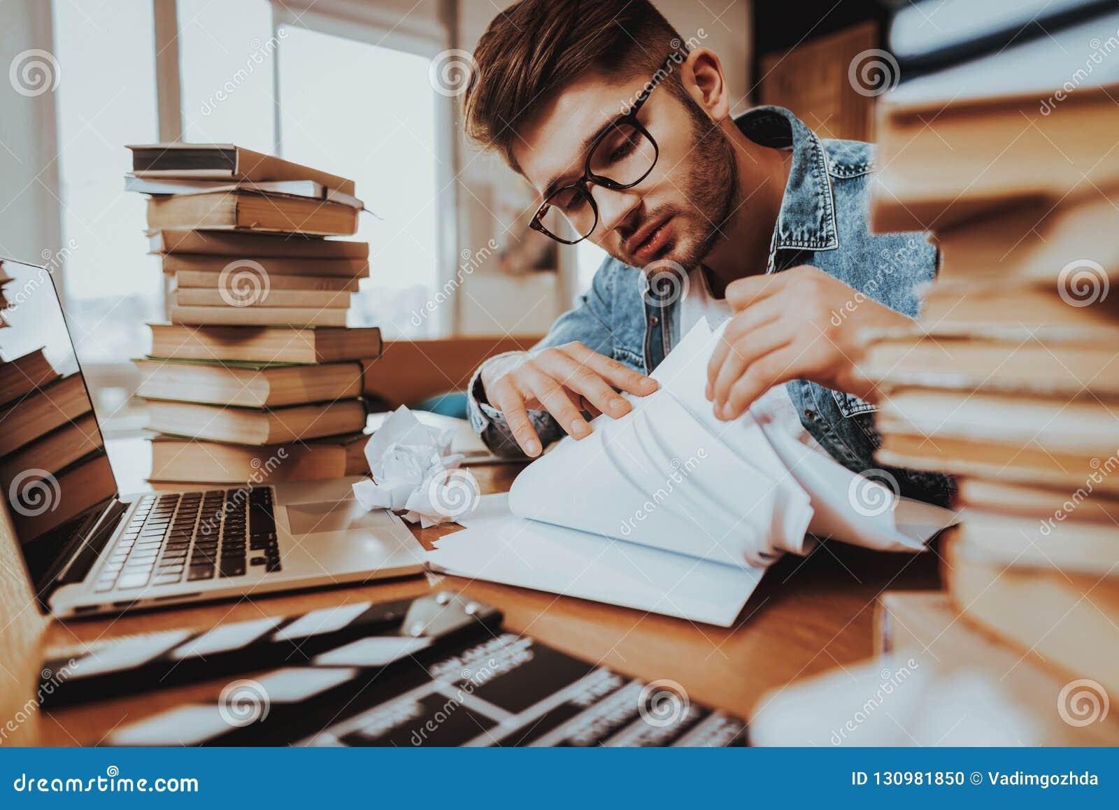De schrijver Working op Laptop zit met Stapel Boeken