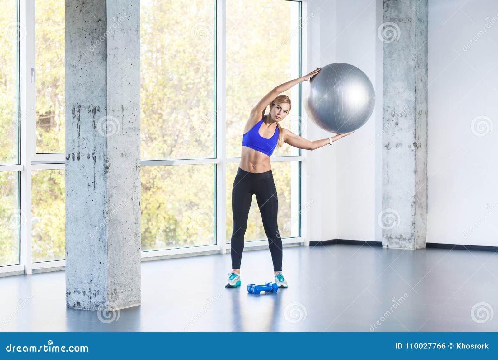 De schuine standpartij van de blondevrouw, die geschikte bal houden