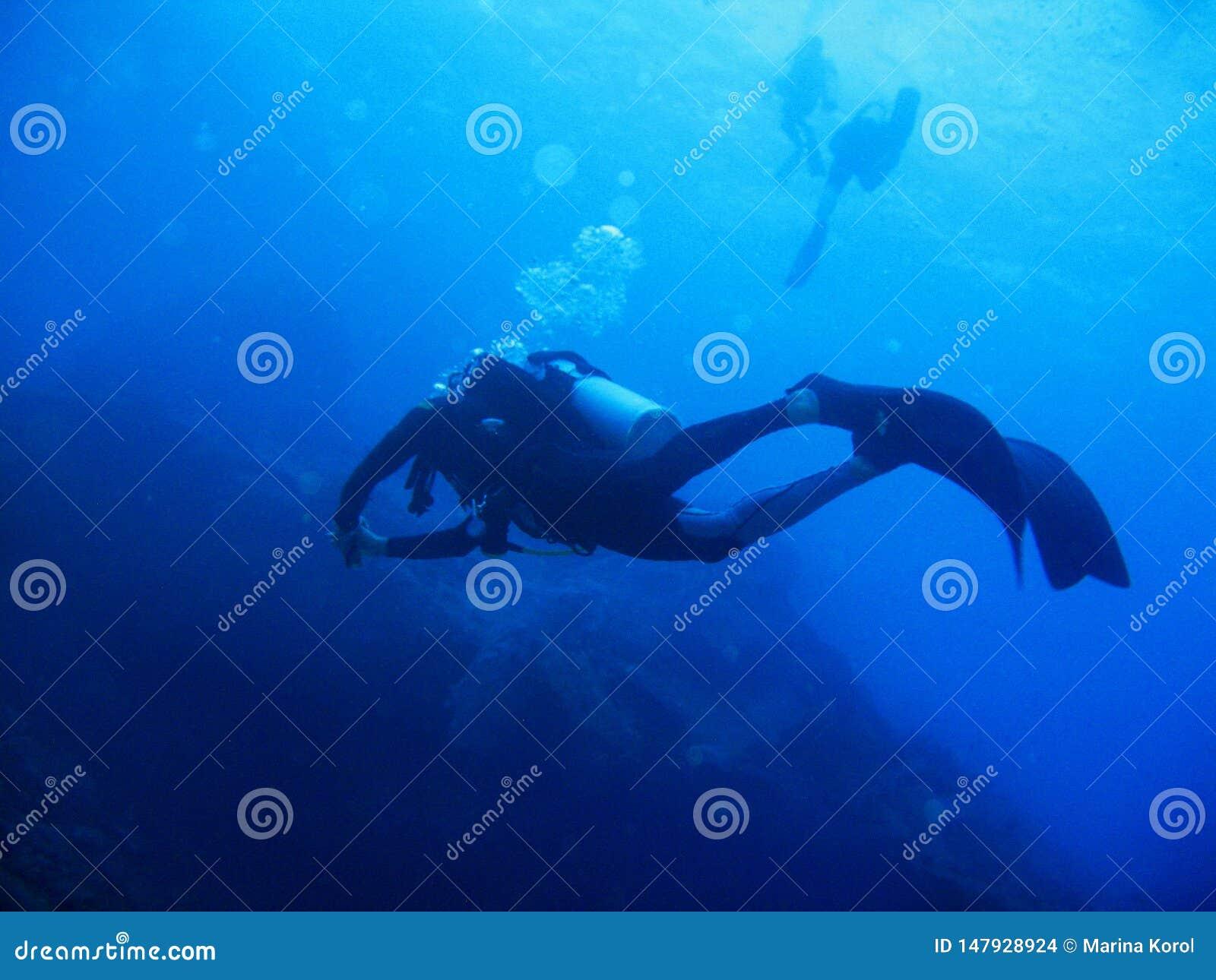De scuba-duiker met volledig materiaal is onderwater Zonlicht en bellen Twee scuba-duikers zijn op de achtergrond