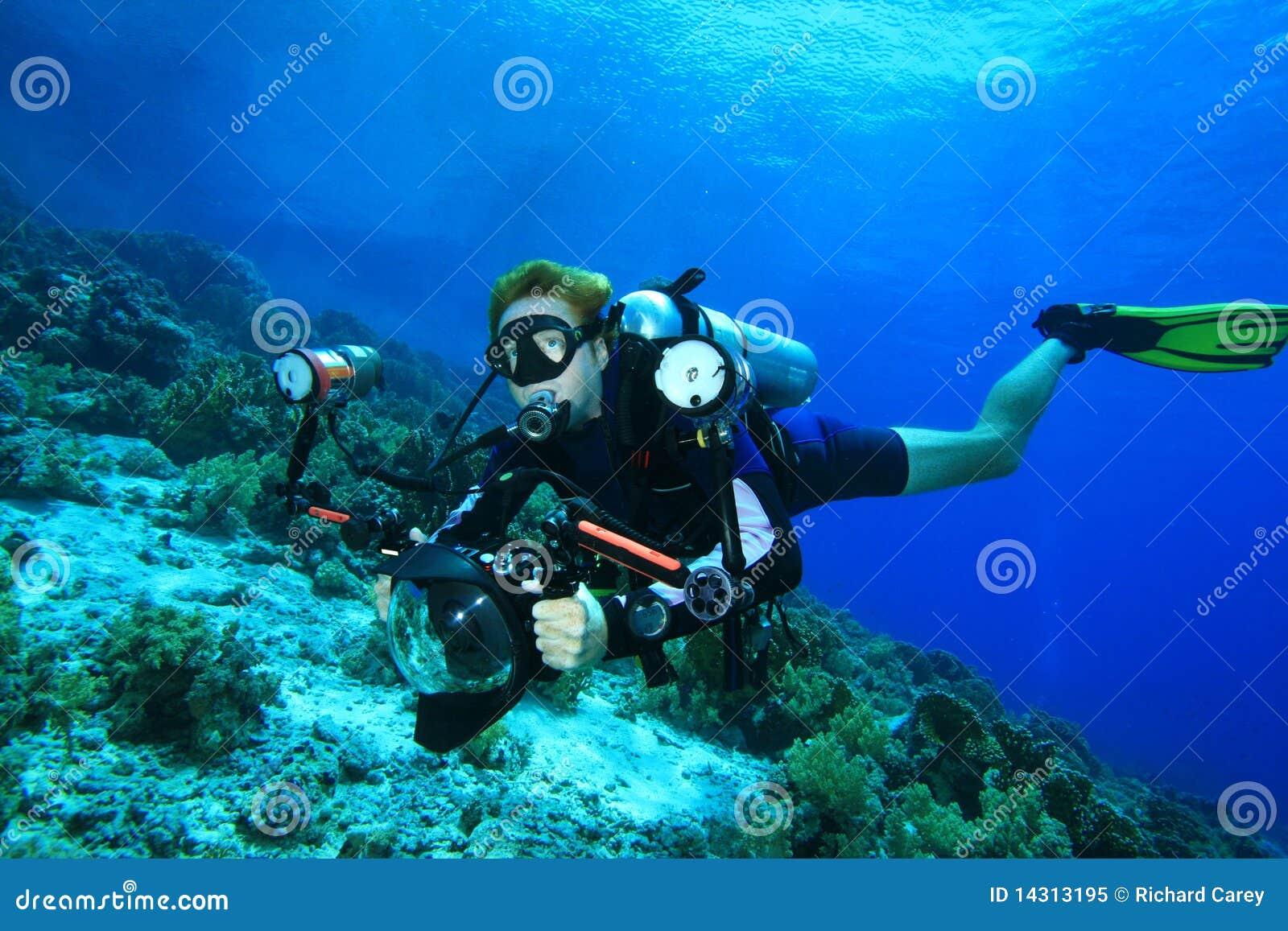 De scuba-duiker onderzoekt koraalrif met zijn camera