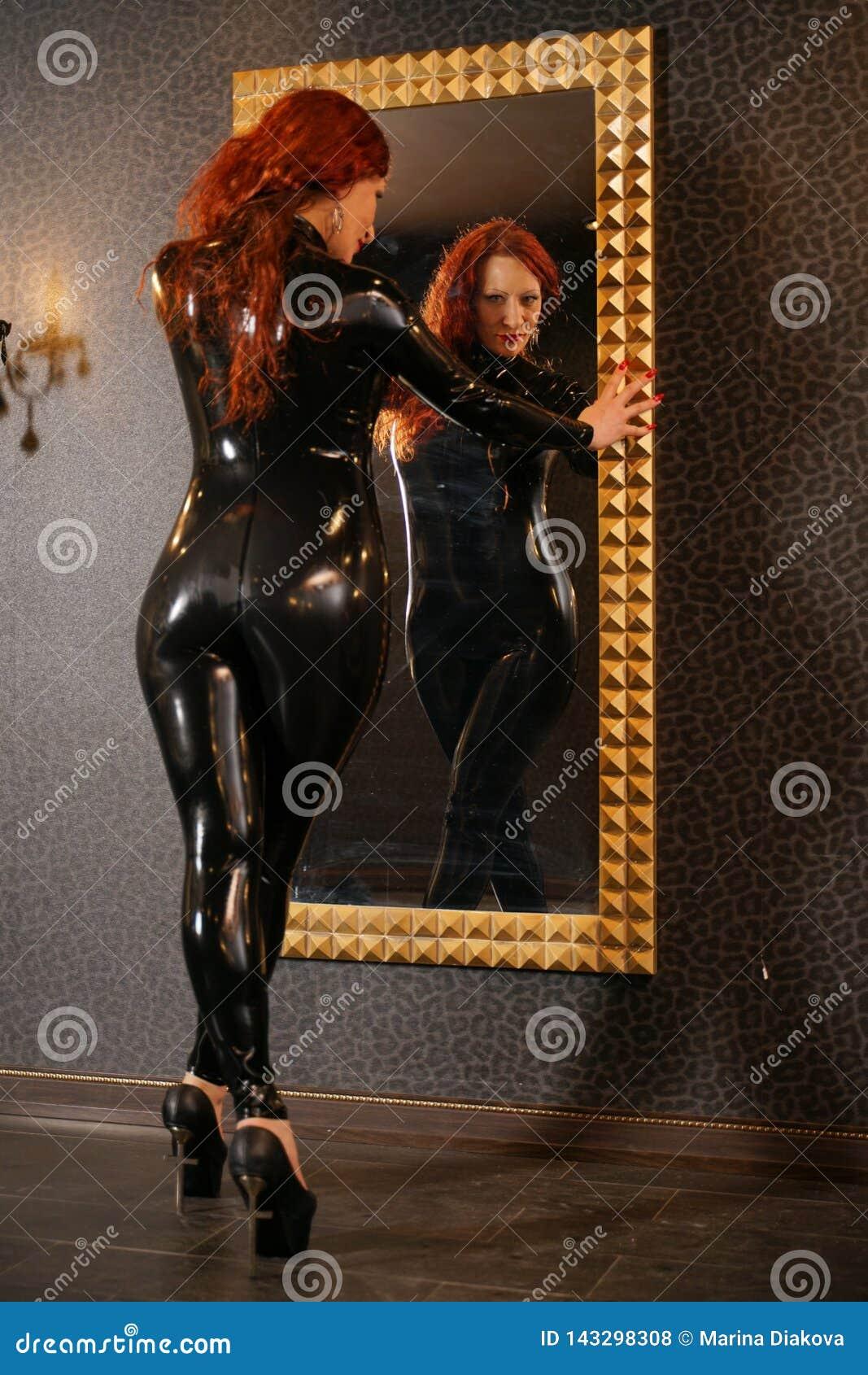 De seksuele vrouw die van het amuletroodharige zwart latexrubber dragen catsuit en de spiegel in donkere ruimte bekijken