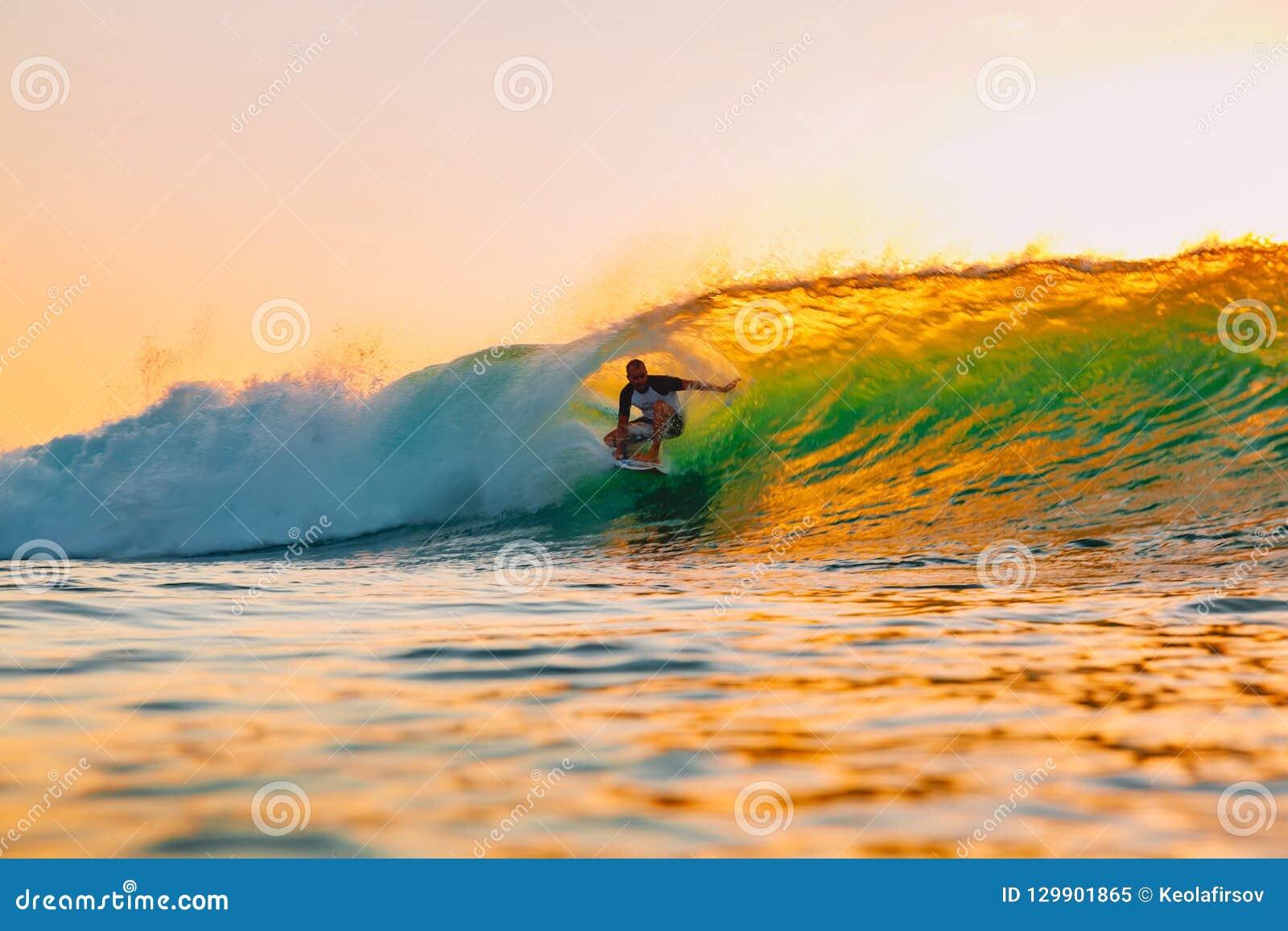 8 de septiembre de 2018 Bali, Indonesia Paseo de la persona que practica surf en onda del barril en la puesta del sol caliente El