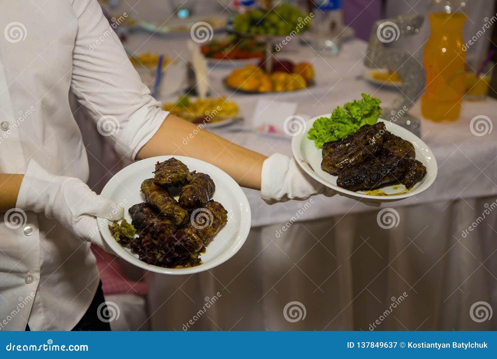 De serveerster in witte handschoenen houdt twee platen met een vleesschotel De diensten van de restaurantcatering