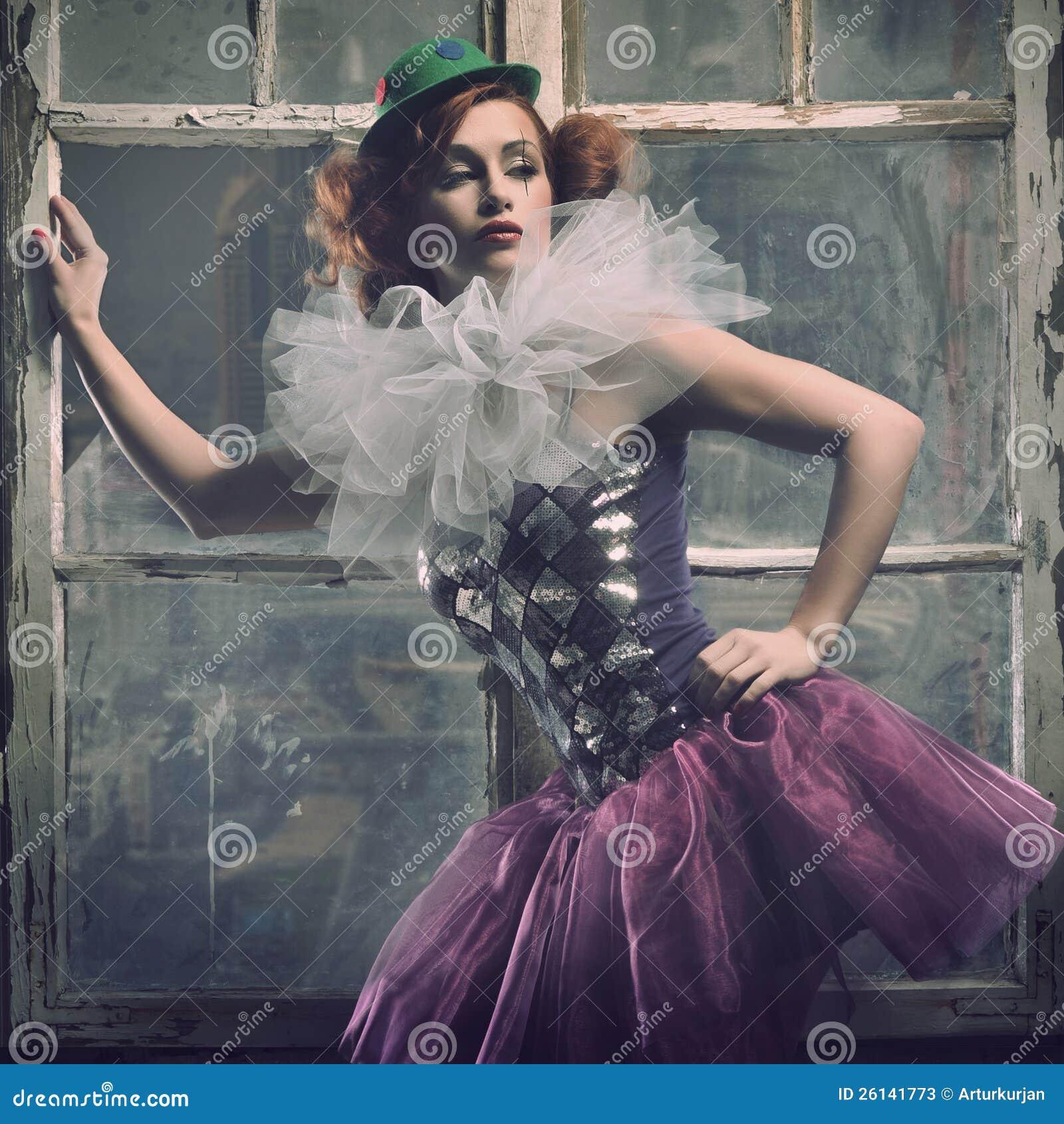 De sexy vrouw van de Pierrot achter het venster